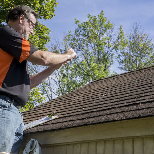 An Insurance Adjuster Takes Photos of Roof Damage.