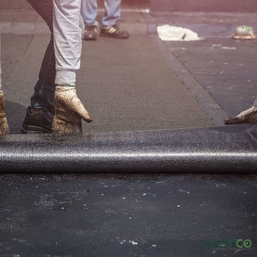 Roofers Roll Out Flat Roofing Material.