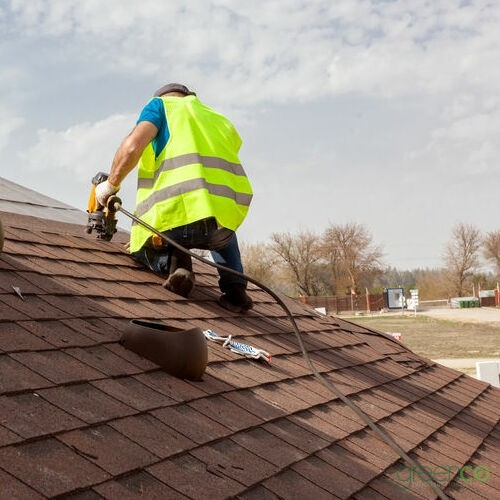 roofer installing shingles onto roof