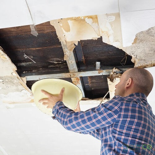 Man Standing With Bucket Under Damaged Area Need Roof Leak Repair